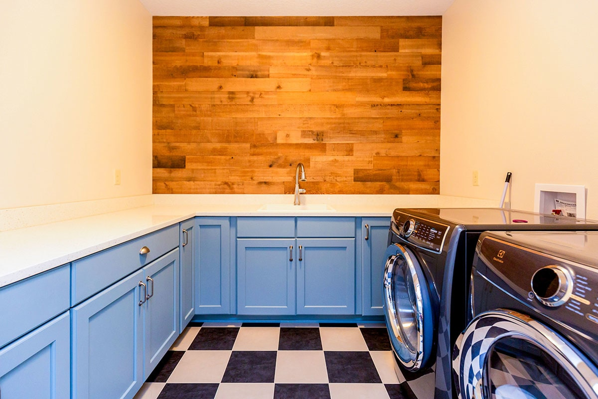 The utility room is filled with blue cabinets, marble countertops, and front load appliances.