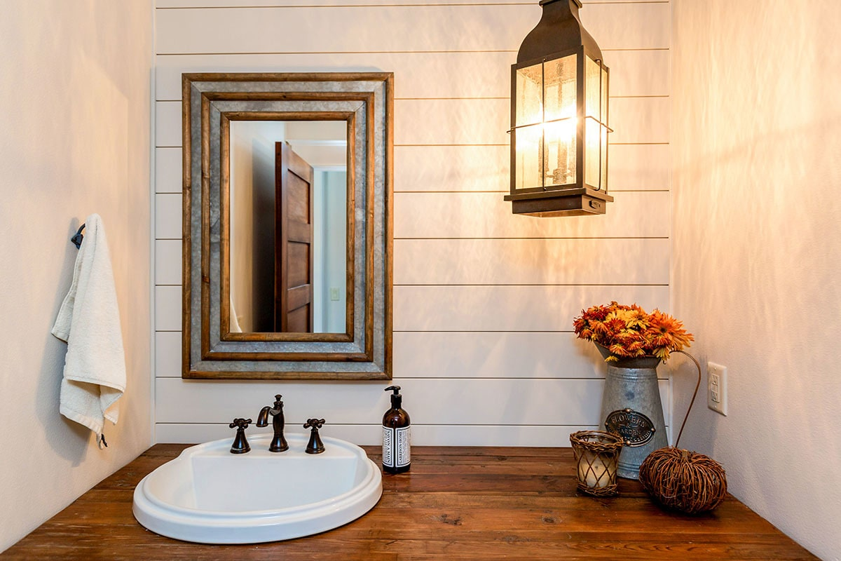 Powder room with a sink vanity illuminated by a lantern pendant light.