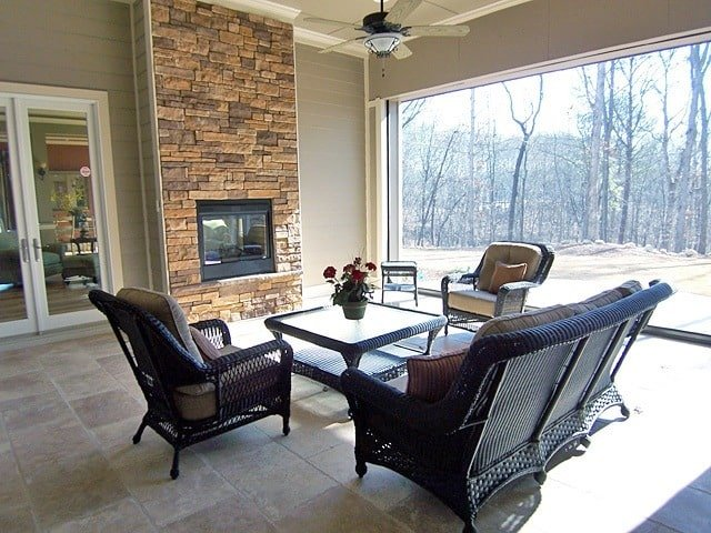 The covered patio has wicker seats, a stone brick fireplace and a panoramic window overlooking the outdoor scenery.