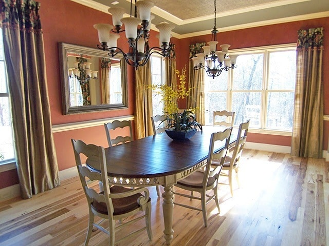 Formal dining room with wrought iron chandeliers, wooden chairs, and an oval dining table.