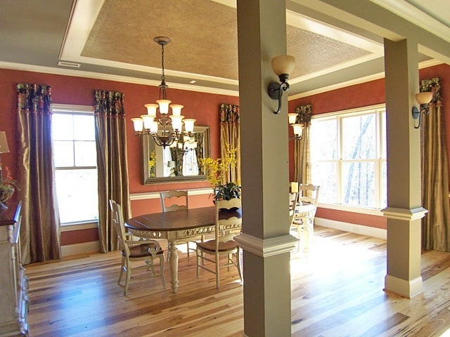 The dining room has a gray tray ceiling, decorative columns, and red walls adorned by a framed mirror.