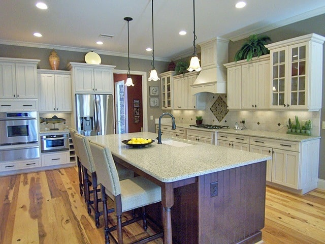 The kitchen is equipped with stainless steel appliances, granite countertops, white cabinetry, and a breakfast island.