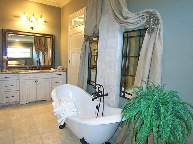 The clawfoot tub is placed under the framed windows that are dressed in flowy drapes.