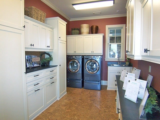 Utility room with front load appliances, white cabinets, granite countertops, and a washstand.