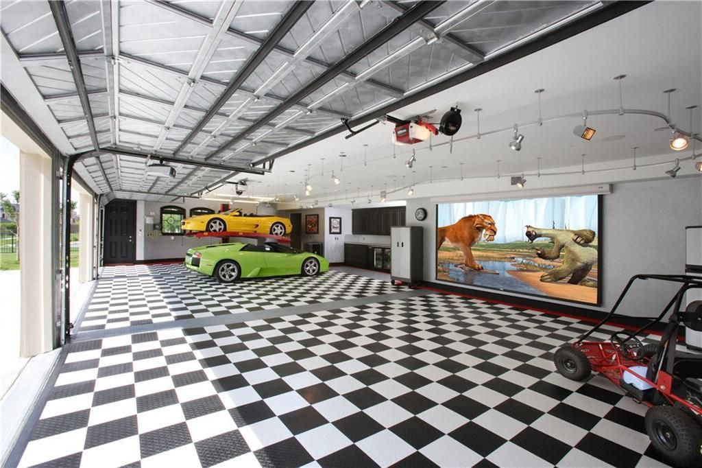 The oversized garage has a metal beamed ceiling, a checkered floor, black cabinets, and a large screen.