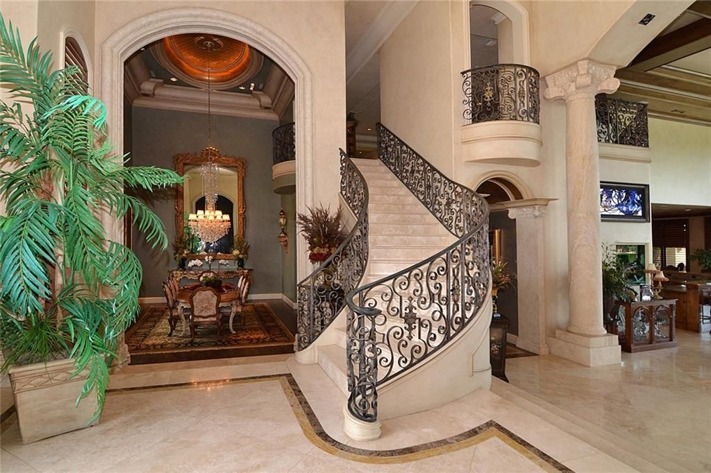 Foyer with a winding staircase framed with ornate wrought iron railings. An archway beside it opens to the formal dining room.