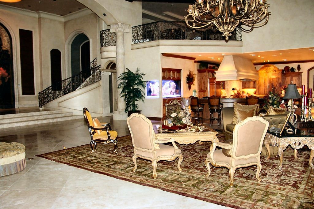 The living room has classy seats, an intricate coffee table, and a grand chandelier.