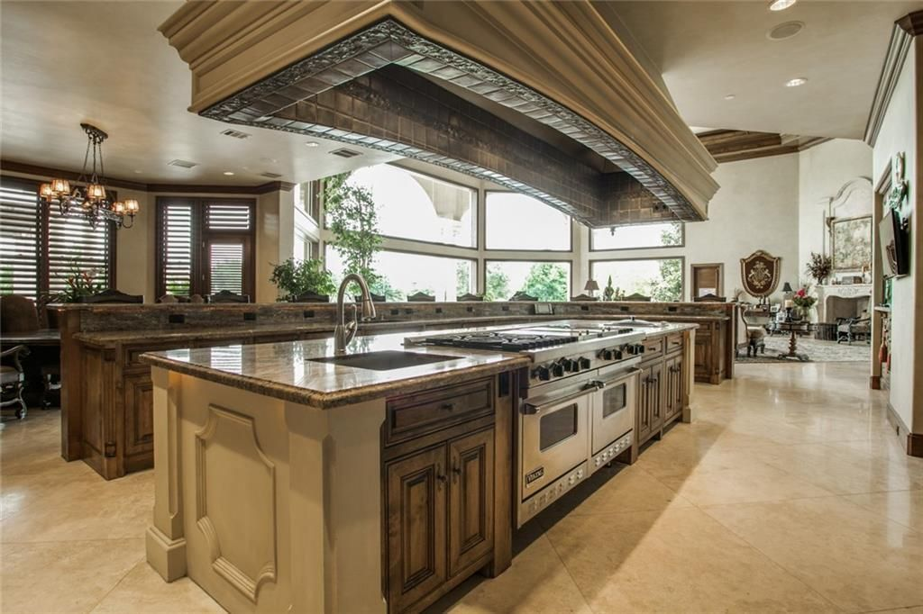 Kitchen with two islands where one has a raised countertop for casual dining and the other one is fitted with a sink and cooking range.