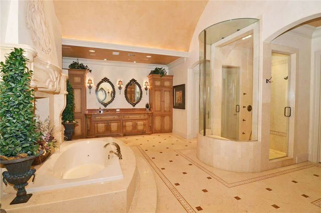 The primary bathroom has a wooden vanity, walk-in shower, and a drop-in bathtub topped with a marble fireplace.