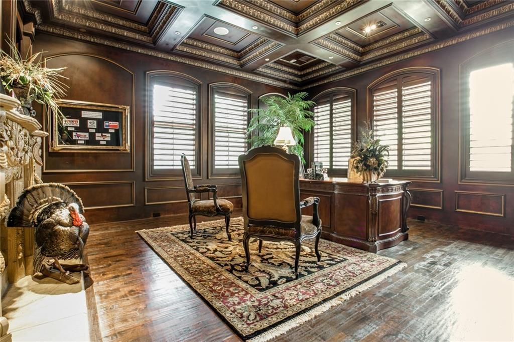The study has a wooden desk, cushioned chairs, and wood-paneled walls that match with the coffered ceiling.
