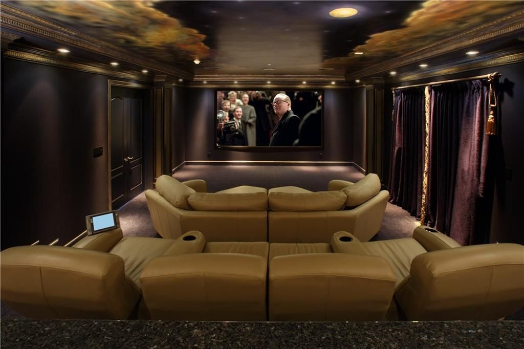 Home theater with black walls, beige leather seats, and a ceiling adorned with a night sky mural.