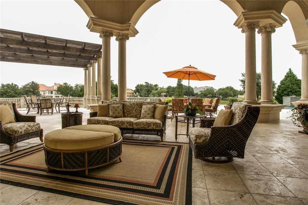 Spacious patio with multiple seating areas, Greek columns, and limestone flooring.