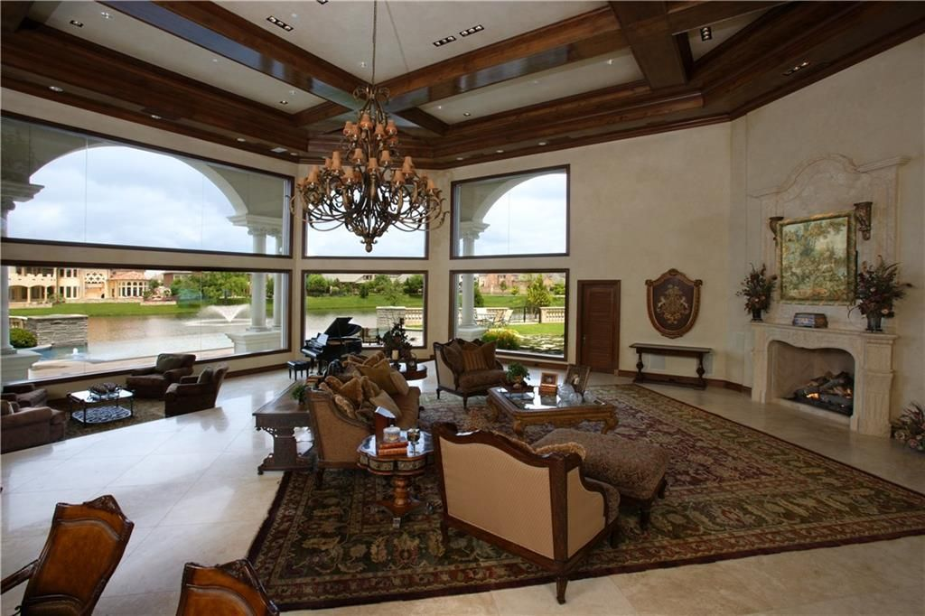 Great room with a fireplace, wooden tables, classy seats, ornate chandelier, and a patterned area rug.