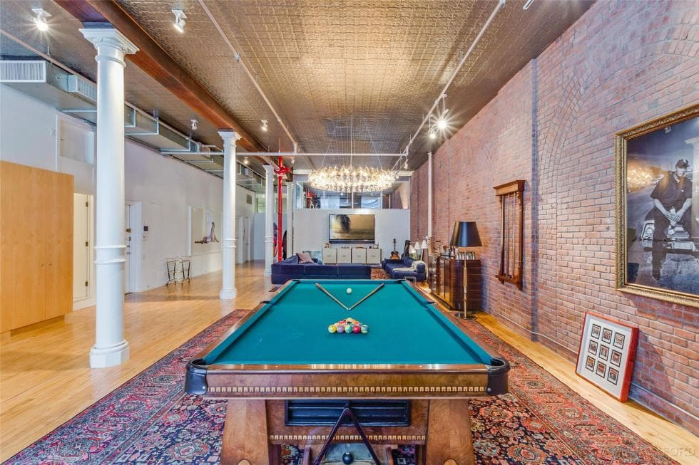 A few steps from the living room area is this game area fitted with a large pool table with a wooden frame that matches the hardwood flooring that is topped with a large area rug. Image courtesy of Toptenrealestatedeals.com.