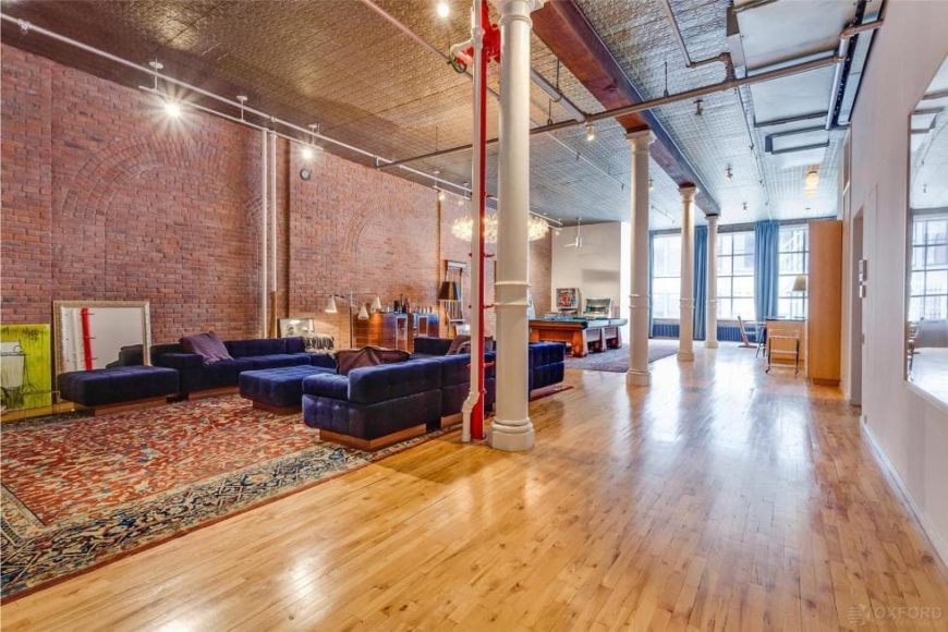 This is a look at the great room with a spacious and airy vibe to its tall ceiling, tall pillars and large windows at the far end that brings in natural lighting for the kitchen, game area and living room area. Image courtesy of Toptenrealestatedeals.com.