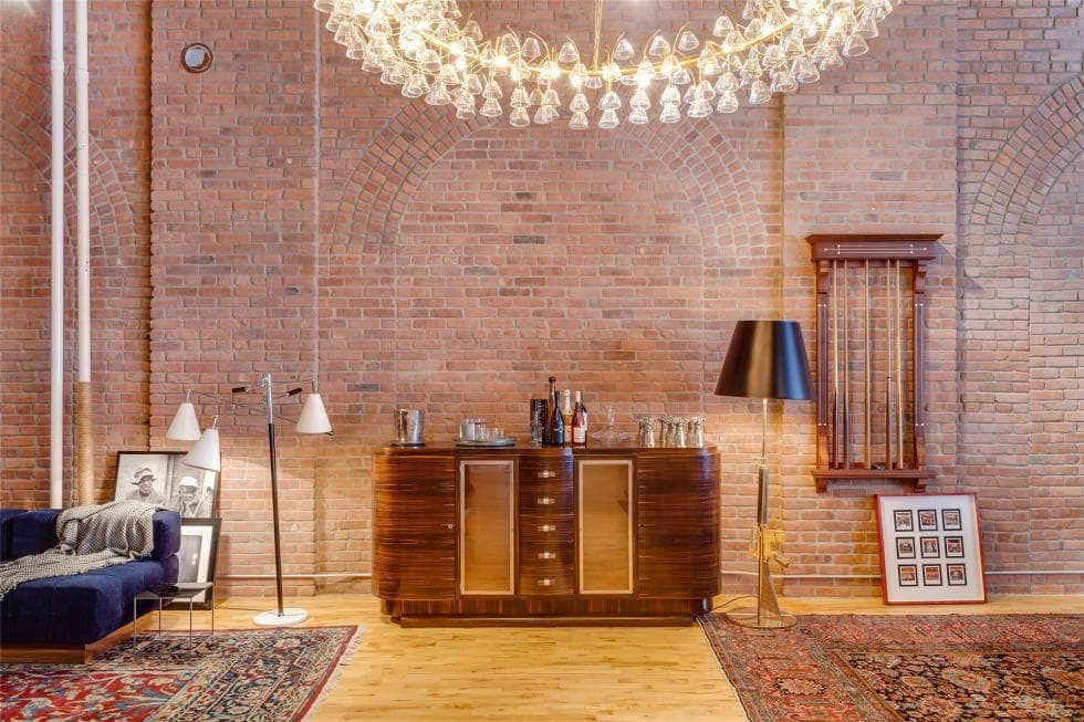 This is the space in between the living room area and the game area. This is fitted with a waist-high wooden cabinet against the red brick wall and a large decorative round lighting. Image courtesy of Toptenrealestatedeals.com.
