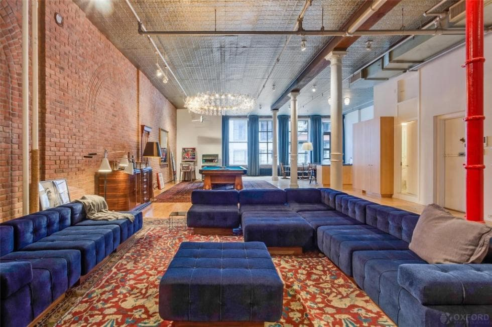 This is a look at the living room that has a dark blue L-shaped sectional sofa set with a cushioned coffee table of the same tone. These stand out against the red patterned area rug and the red brick wall. Image courtesy of Toptenrealestatedeals.com.