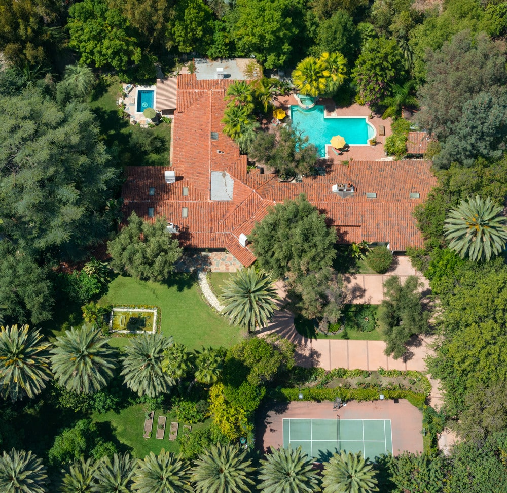 This is an aerial view of the house showing the various outdoor areas of the house like the tennis court, the two pools and the pond in the middle of the grass lawn. Image courtesy of Toptenrealestatedeals.com.