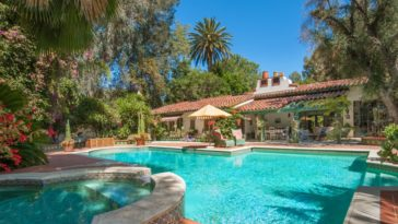 This is a look at the back of the hacienda-style house from the vantage of the backyard pool with an attached spa. Here you can see the terracotta elements of the house adorned by the lush landscaping that surrounds it. Image courtesy of Toptenrealestatedeals.com.