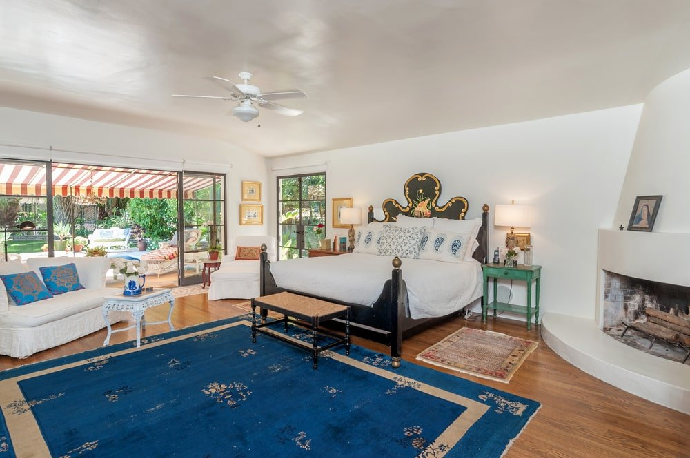 The primary bedroom has a large dark wood four-poster bed adorned with a alrge blue area rug and bedside tables bearing lamps. Image courtesy of Toptenrealestatedeals.com.