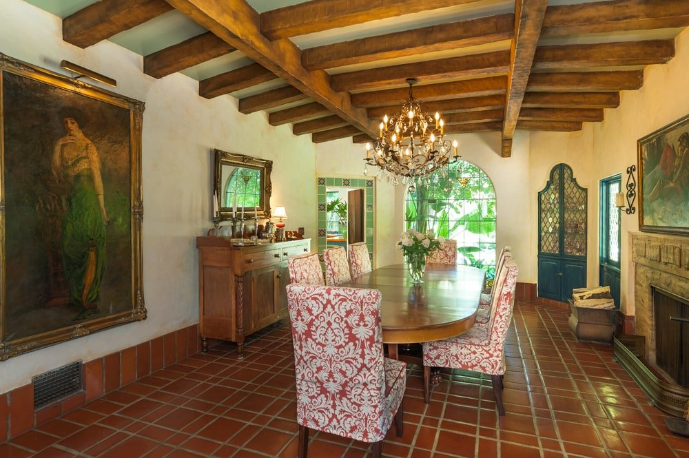 This other view of the dining room shows the cove ceiling with exposed beams and a chandelier over the table. Image courtesy of Toptenrealestatedeals.com.
