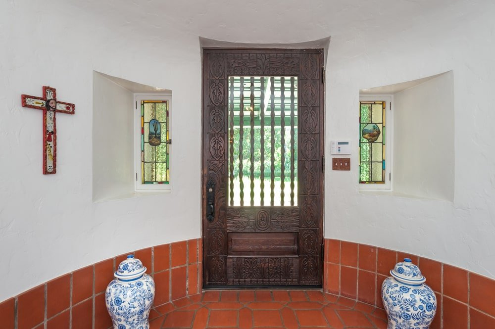 This is a close look at the main door from the vantage of the foyer. It has a dark wood tone that stands out against the bright beige walls with small stained glass windows. Image courtesy of Toptenrealestatedeals.com.