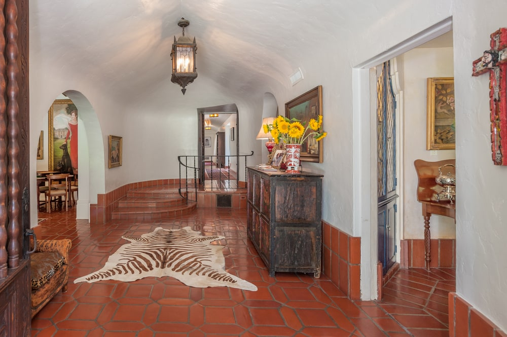 This is the foyer with terracotta flooring tiles adorned by the animal fur area rug and the dark wood cabinet on the side. Image courtesy of Toptenrealestatedeals.com.