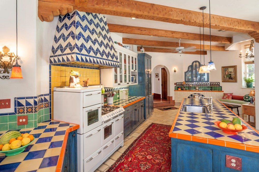 The kitchen's patterned blue tiles and blue cabinetry make the white cooking area stand out. Image courtesy of Toptenrealestatedeals.com.