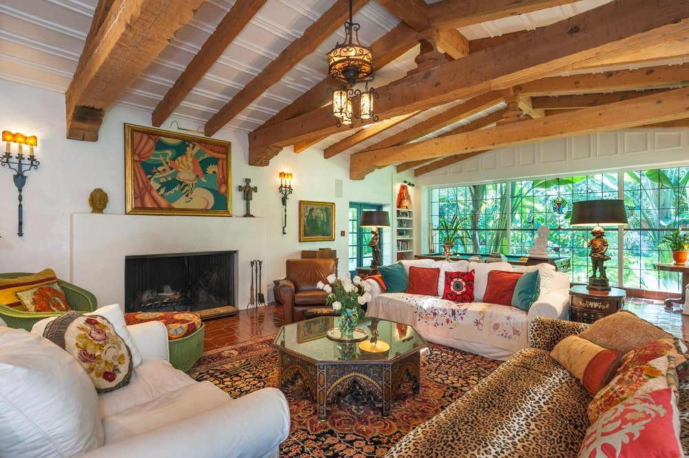 The living room has a bright beige sofa set, glass-top dark brown coffee table and a large fireplace adorned with a large painting. Image courtesy of Toptenrealestatedeals.com.