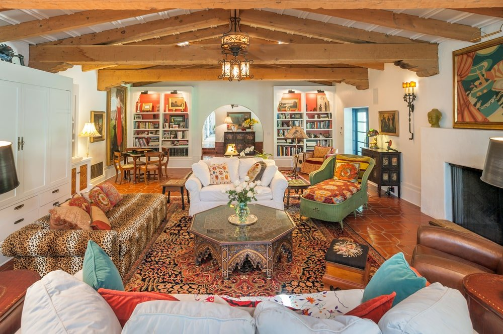 This other look at the living room showcases the cathedral ceiling with exposed wooden beams that stand out against the bright walls. Image courtesy of Toptenrealestatedeals.com.
