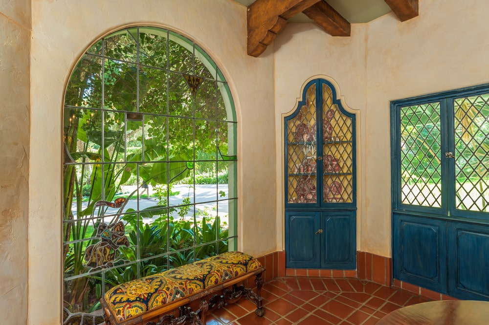 This is a reading nook with a cushioned bench under a large arched window. Image courtesy of Toptenrealestatedeals.com.