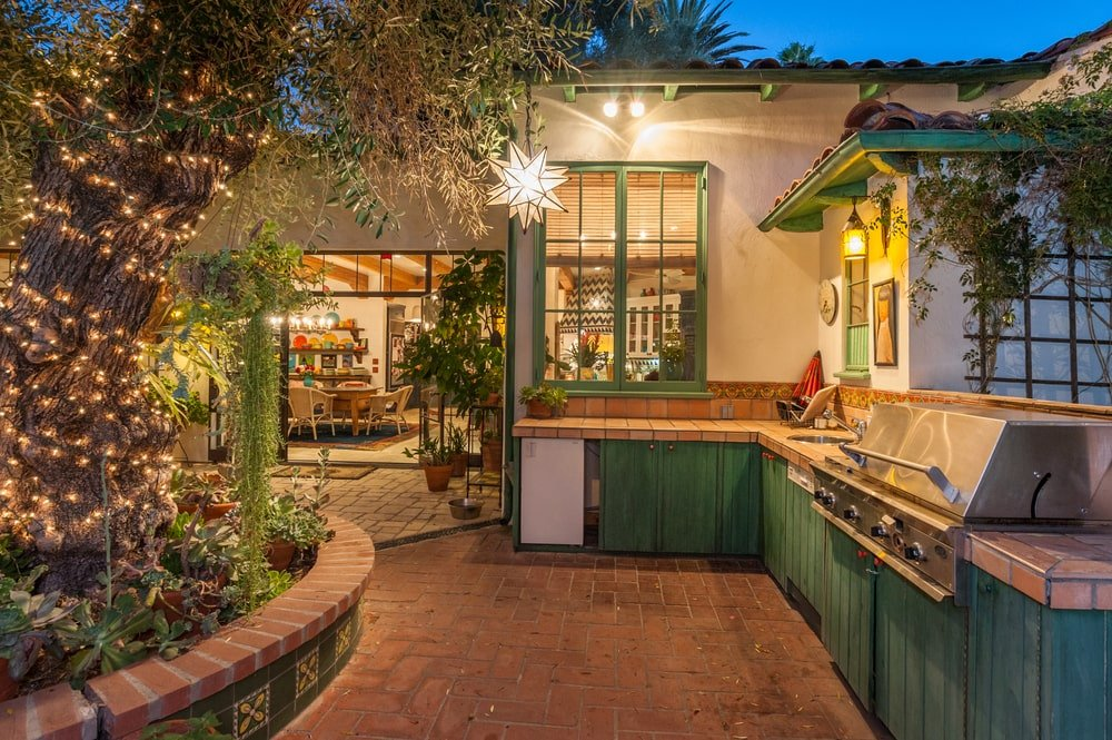 The outdoor kitchen has terracotta tiles and green cabinetry that matches the window frames. Image courtesy of Toptenrealestatedeals.com.