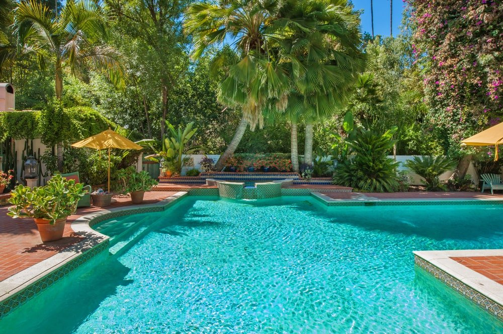 The backyard swimming pool has an attached spa-style small pool at the far end under the shade of the tall trees. Image courtesy of Toptenrealestatedeals.com.