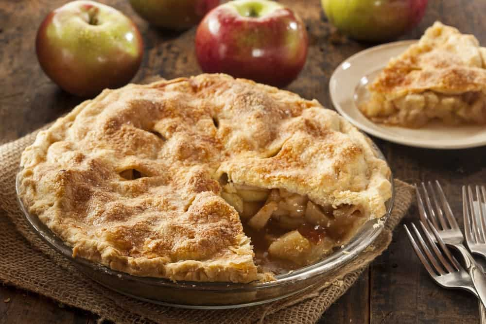 Homemade organic apple pie beside apples and forks on wooden table.