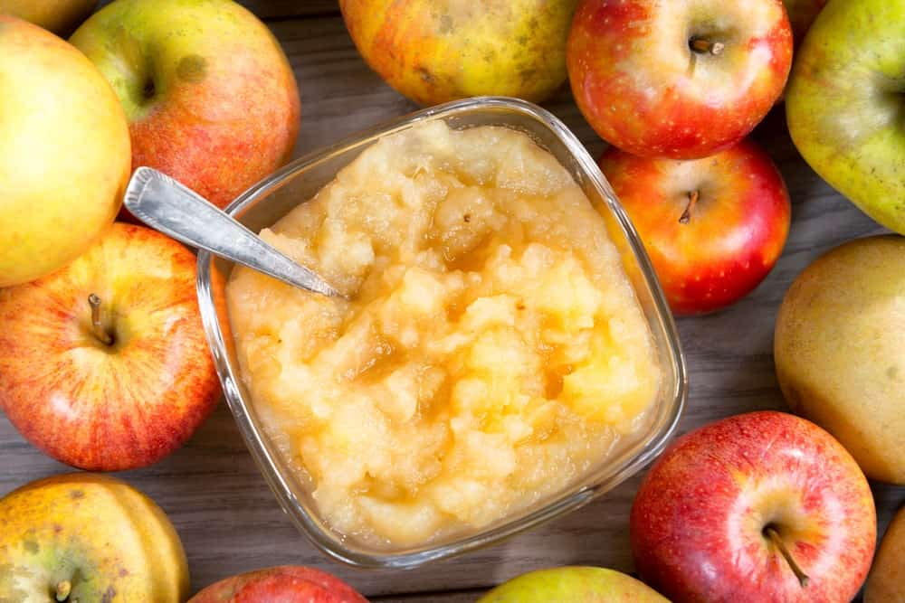 A serving of applesauce surrounded by apples.