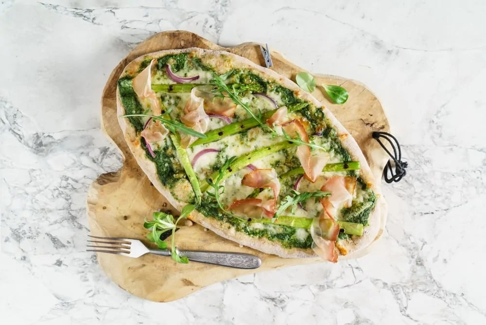 Top view of asparagus pizza against the marble countertop.