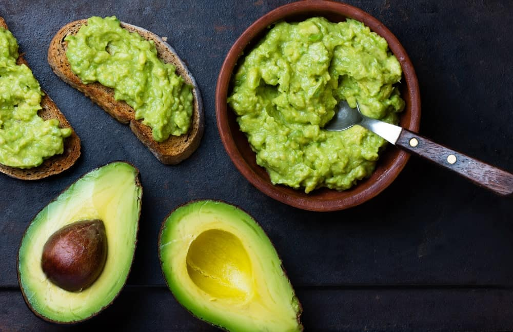 A bowl of avocado spread applied to a couple of toasts.