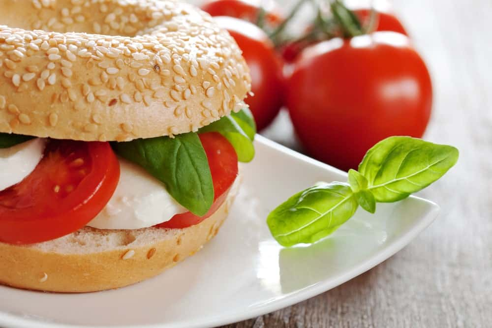 A plate of bagel and tomato sandwich with fresh tomatoes on the side.