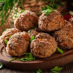 A mound of baked meatballs on a chopping board.