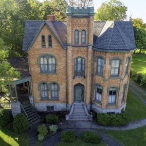 This is an aerial view of the front of the stone and brick mansion with large windows and a lush landscape of shrubs and trees. Image courtesy of Toptenrealestatedeals.com.