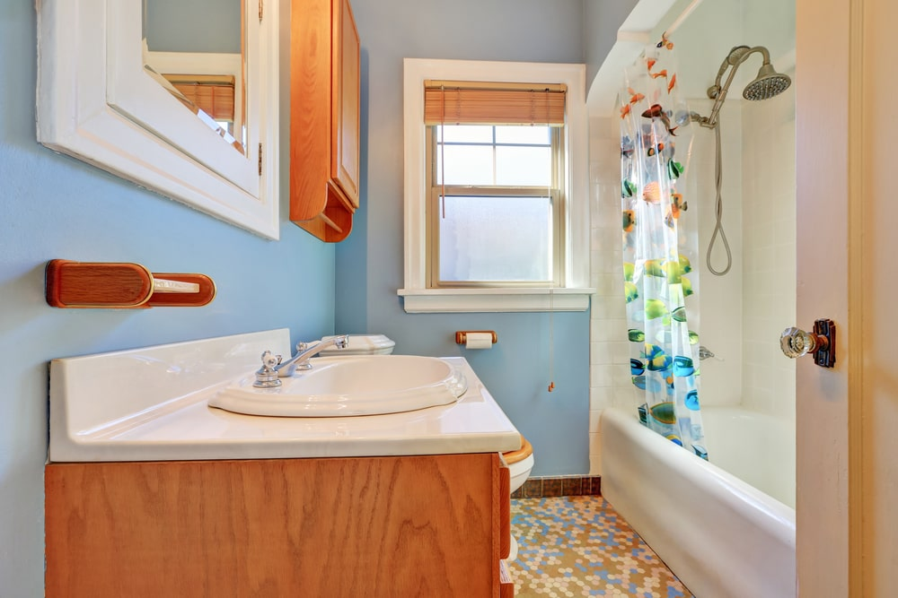 Bathroom interior with blue walls, wooden cabinetry, a window, and an alcove tub/shower combo.