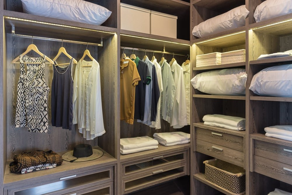 A look inside a walk-in closet with built-in drawers, shelves and racks.
