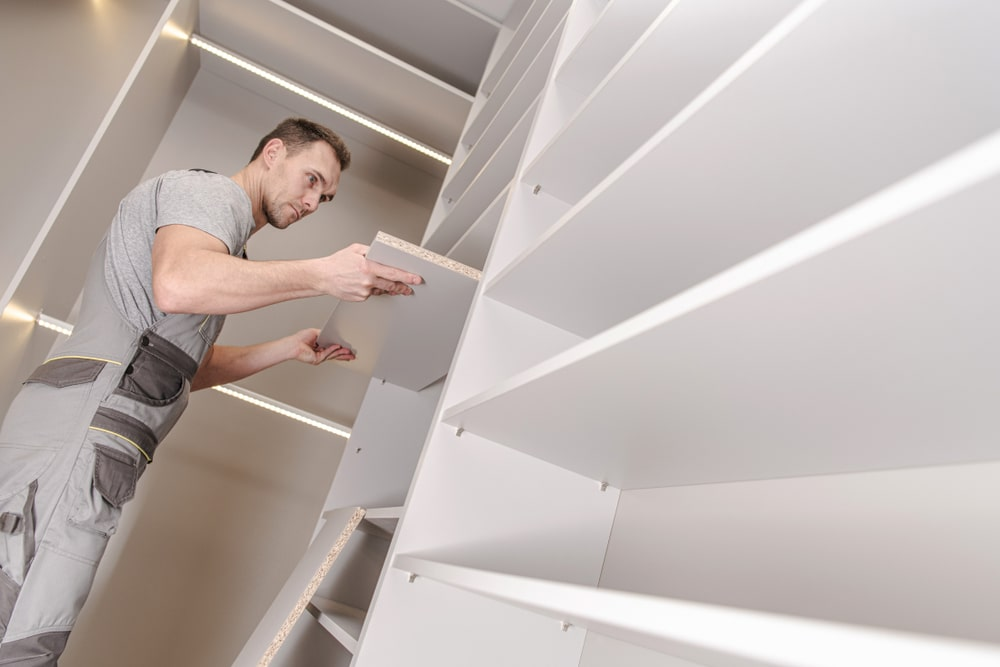 A man installing shelves at the closet.