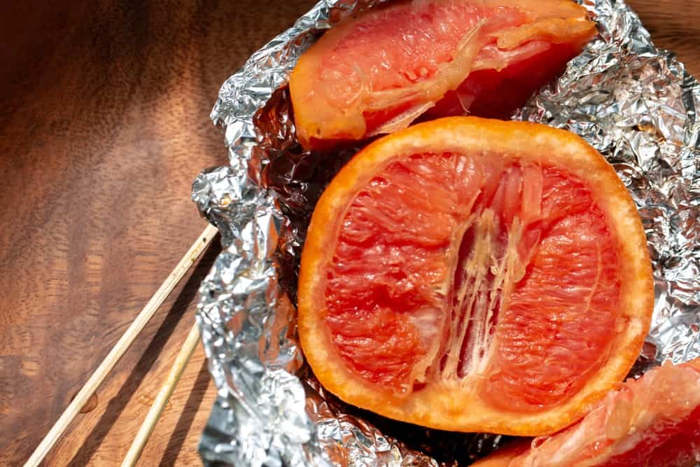 Slices of broiled grapefruit in a tin foil against wooden background.