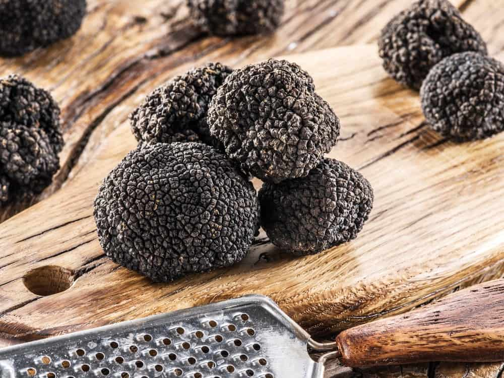 Burgundy truffles and a grater on a wooden chopping board.