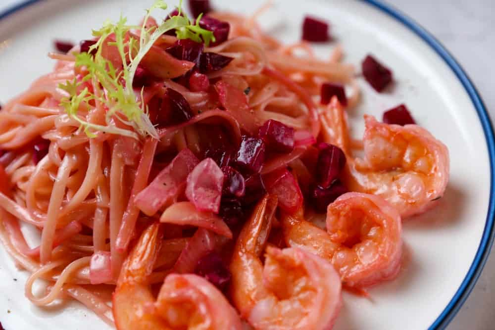 Red cabbage spaghetti with shrimp heads in a plate.