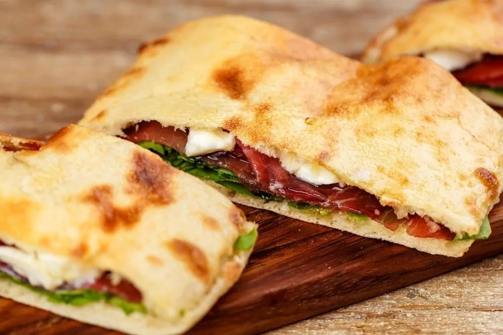 Calzones on a wooden chopping board.