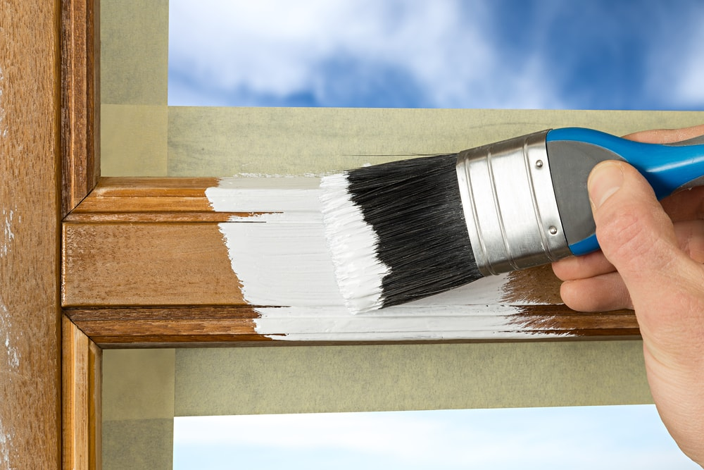 A wooden window frame being painted white with a brush.
