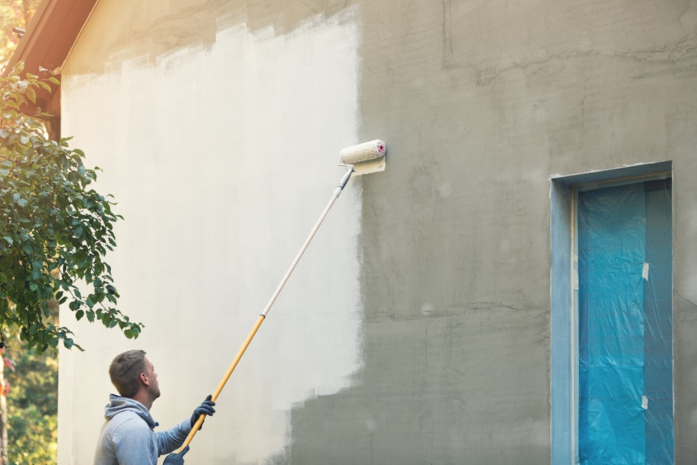 A man painting the tall concrete exterior wall using a roller.