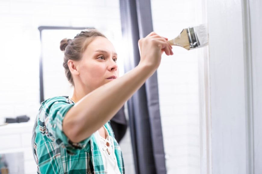 A woman painting the wall of her bathroom.